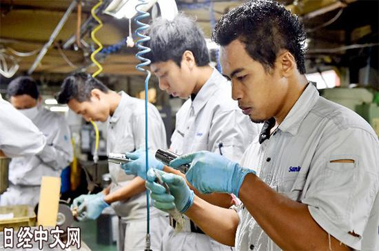 在日本三共制作所总社工厂里上班的外国人(大阪府东大阪市,资料图)