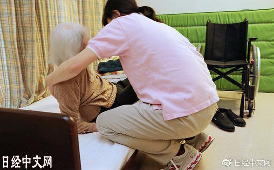看护设施的工作人员正在照顾老年痴呆症患者