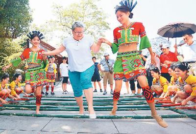 在海南三亚市南山景区,黎族阿妹和外国游客跳起竹竿舞。  陈文武摄(人民图片)