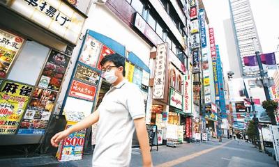 图为一名男子戴着口罩走在日本东京街头。